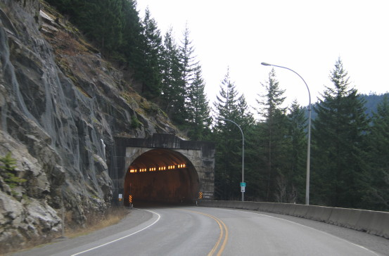 A winding highway leads into a tunnel built into a rock face.