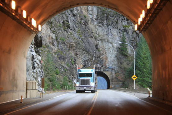 A semi truck exits one tunnel and heads into another.