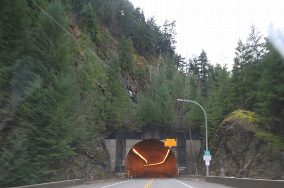 Approaching a highway tunnel aglow with overhead lighting.