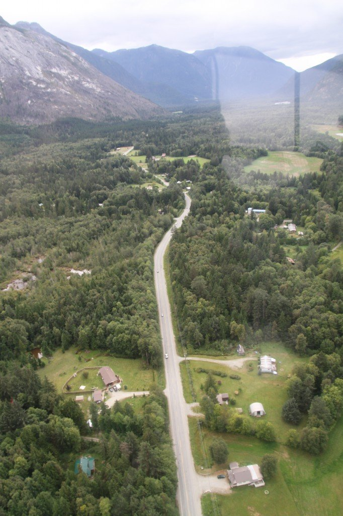 Aerial view of a highway traveling through a small town, towards a mountain range.