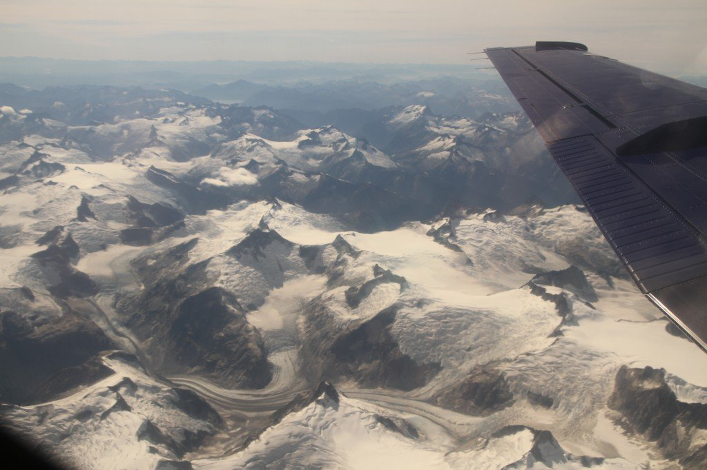 Looking out at snow-covered mountain peaks from the window of an airplane.