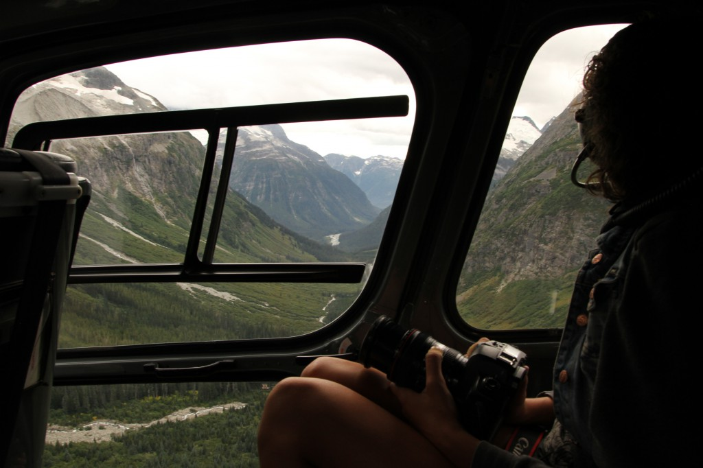 A woman sits in a helicopter, traveling over a mountain valley.