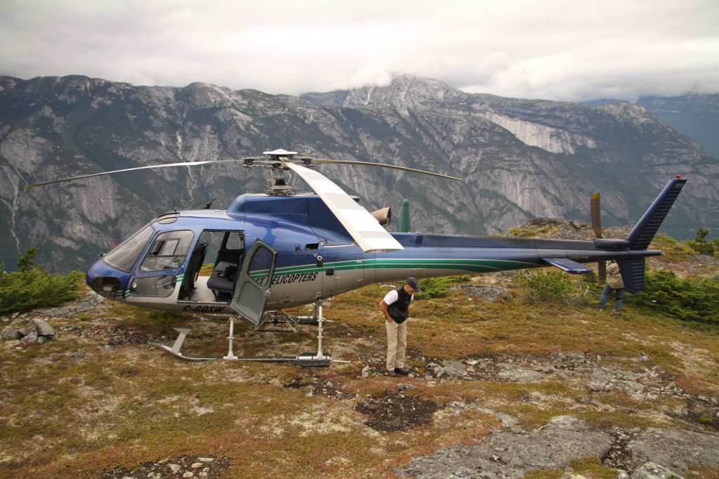 A man stands next to a helicopter perched on a mountain top.