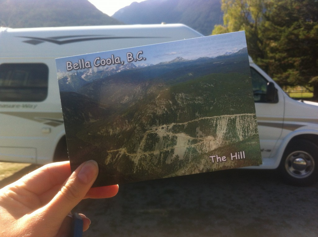 "A hand hold up a postcard of a rolling landscape that says ""Bella Coola, B.C. The Hill""."