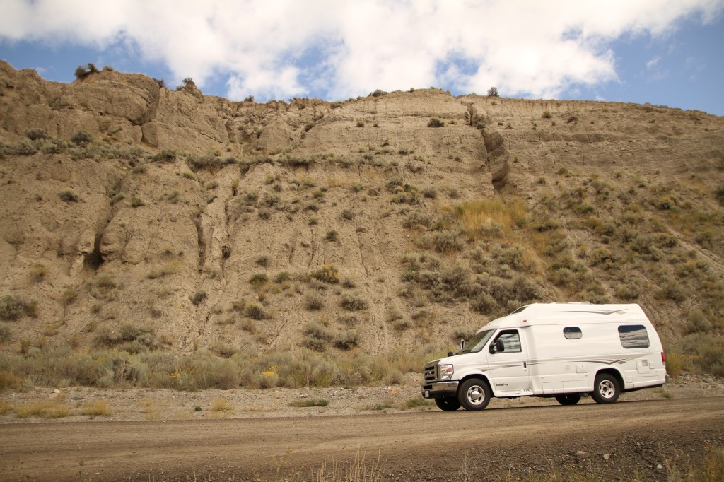 An RV drives past a rocky embankment.