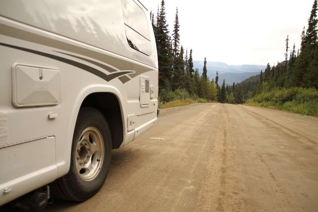 An RV pulled over to the shoulder of a dirt road.