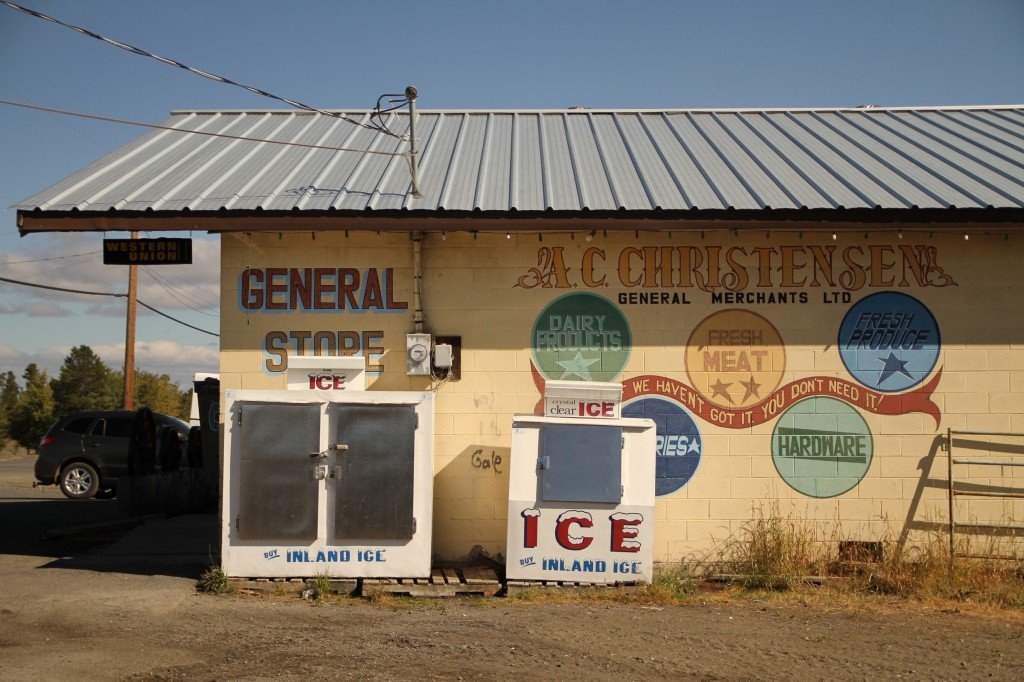 Exterior of a colourful general store with two ice machines.