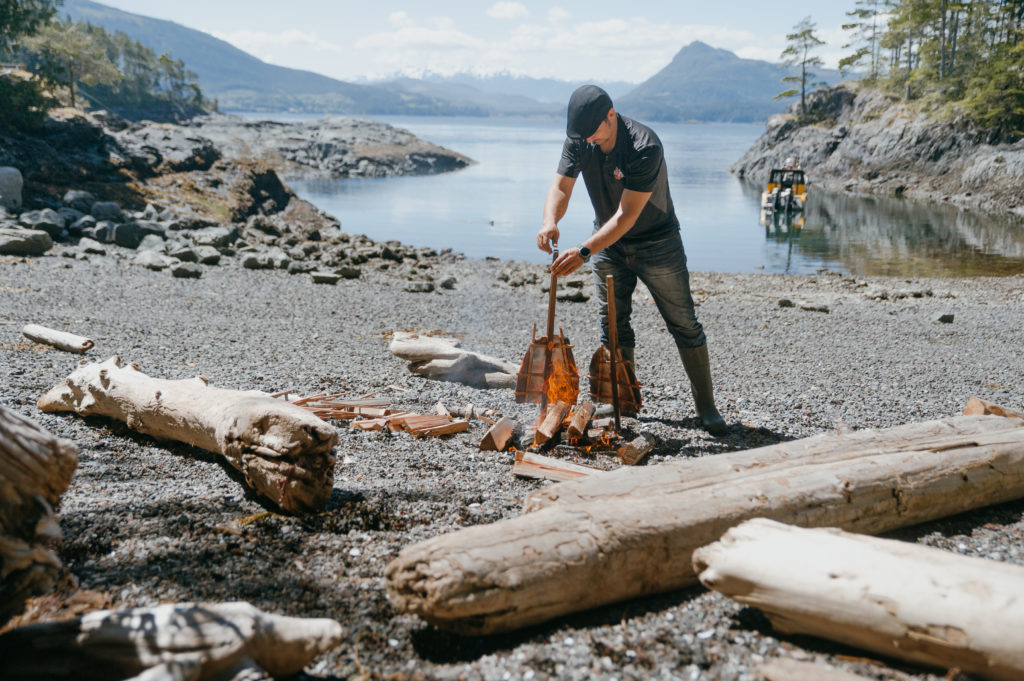 A man smokes two salmon fillets over a campfire.