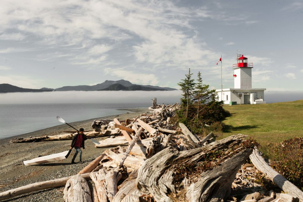 A lighthouse sits on the coast of a rocky beach, overlooking water and mountains.
