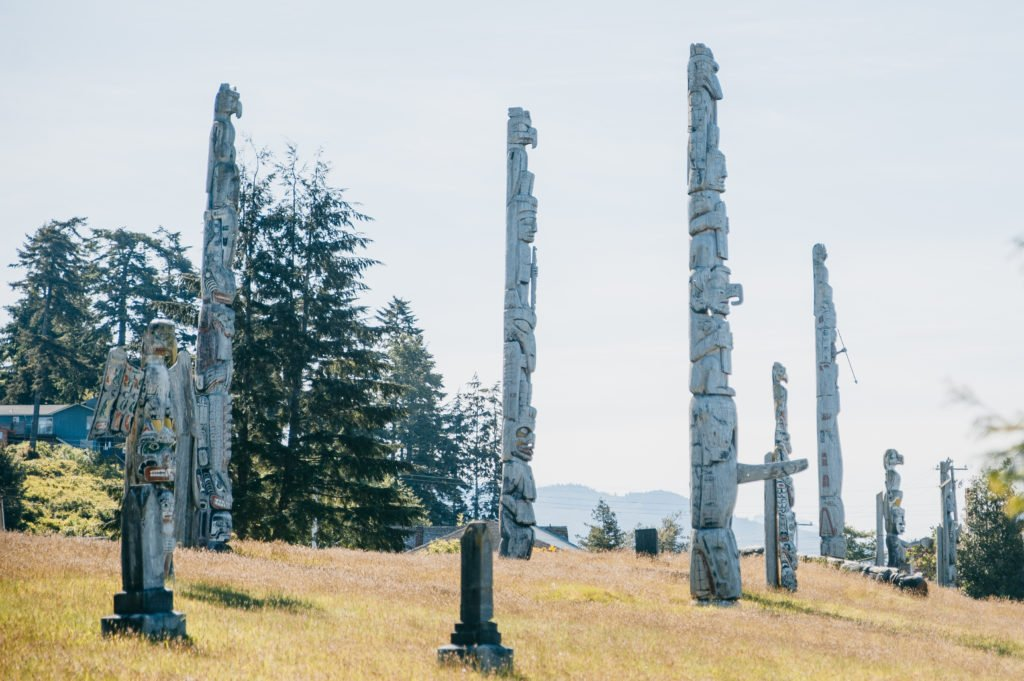 A hill dottes with intricate totem poles.