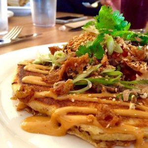A dish of roast duck pancakes topped with homemade kimchi and sesame seeds.