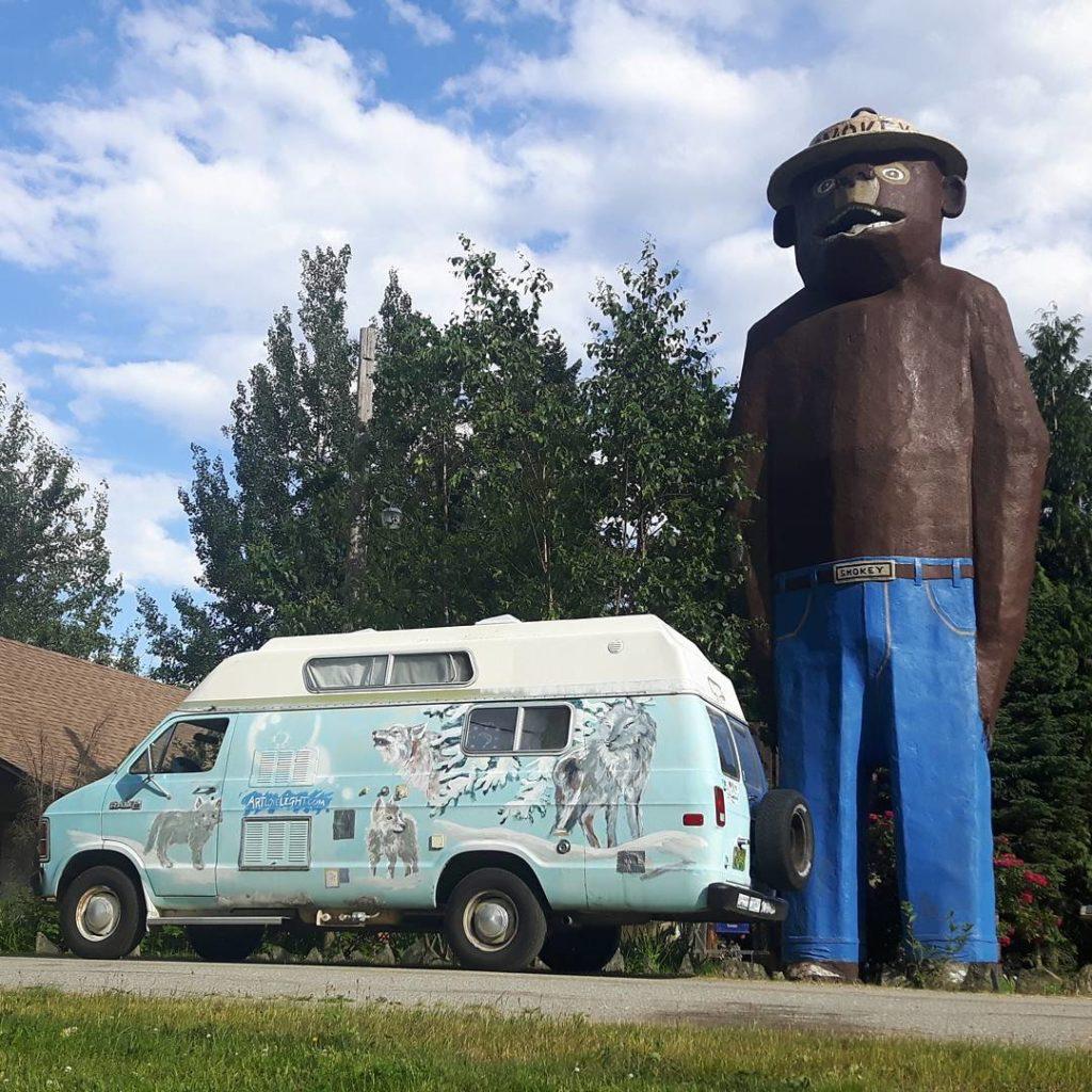 A giant statue of Smokey Bear next to a VW wagon.