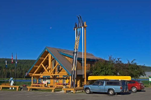 40-foot tall skis next to a log cabin.