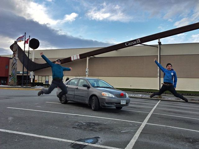 Two young men jump in the air in front of the world's largest hockey stick.
