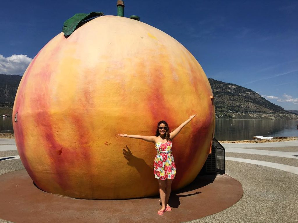 A woman poses in front of a statue of a giant peach.