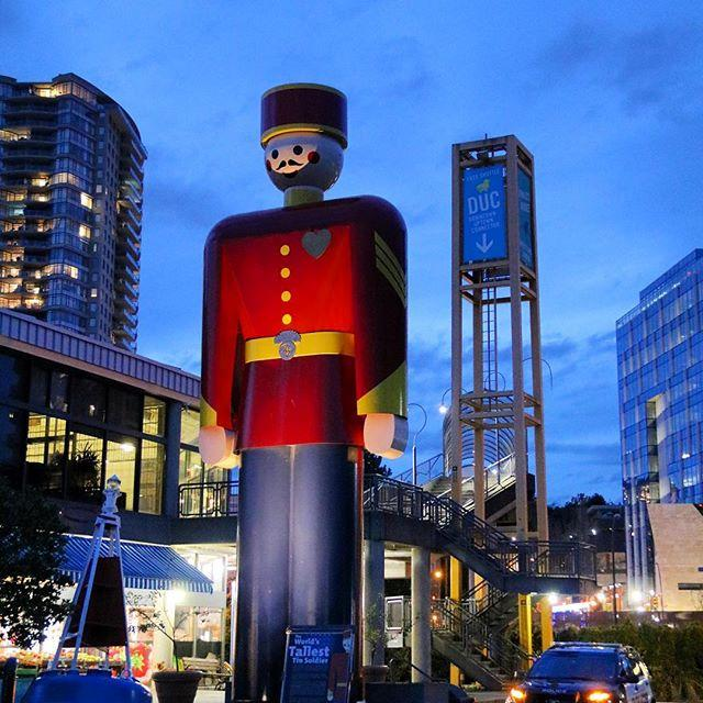 The world's tallest tin soldier stands in the middle of a busy downtown area.