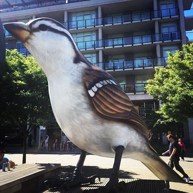 People stroll past a statue of a giant sparrow.