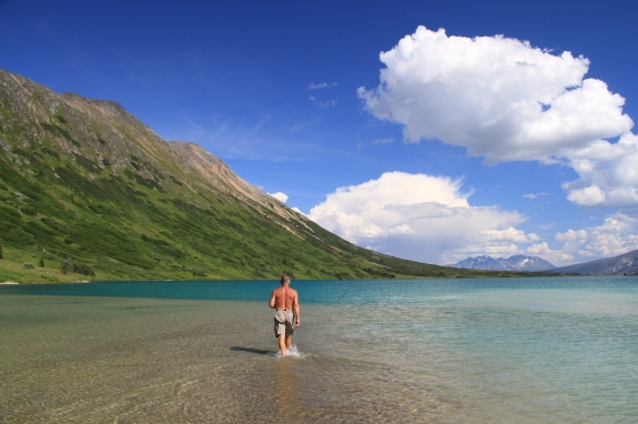 A man in swim trunks wades through the shallow waters of a lake.