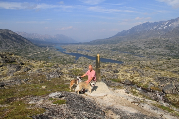 A man poses with his two dogs in the middle of a rocky landscape.