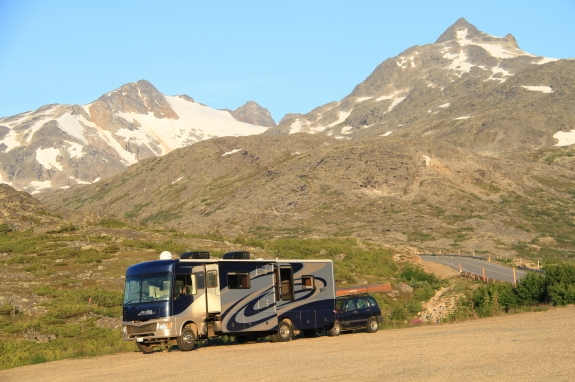 An RV parked at the bottom of a mountain range.