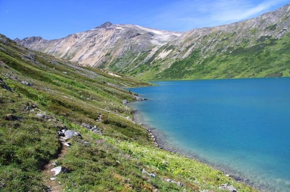 A small lake nestled at the base of a mountain range.