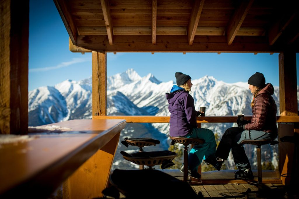 Two woman in ski jackets enjoy coffee on an outdoor patio with views of snow-covered mountains.