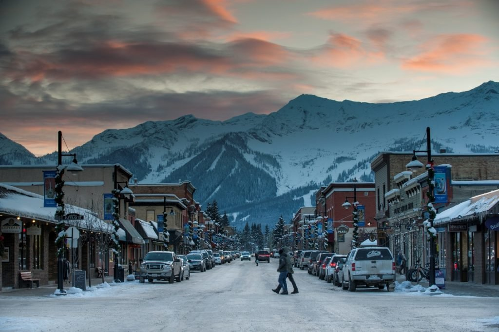 A quiet town at the base of a snow-covered mountain under an orange sunset.