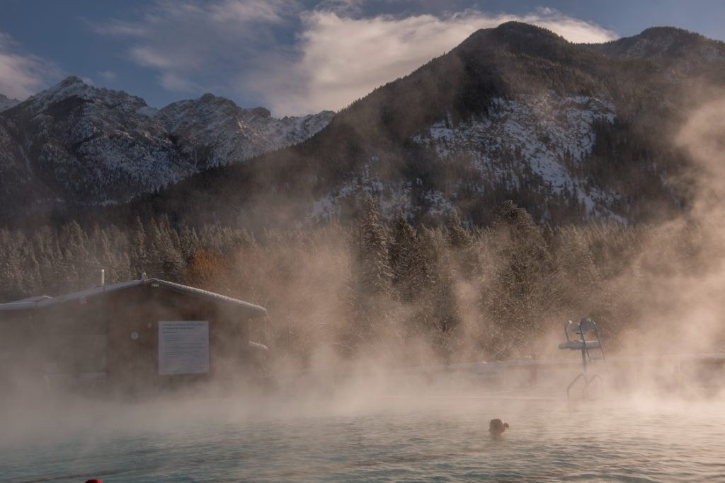 A woman relaxes in a hot spring with view of snow-covered mountains.