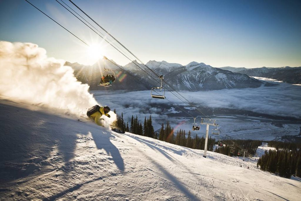 A snowboarder shreds down a hill, under the ski lift.