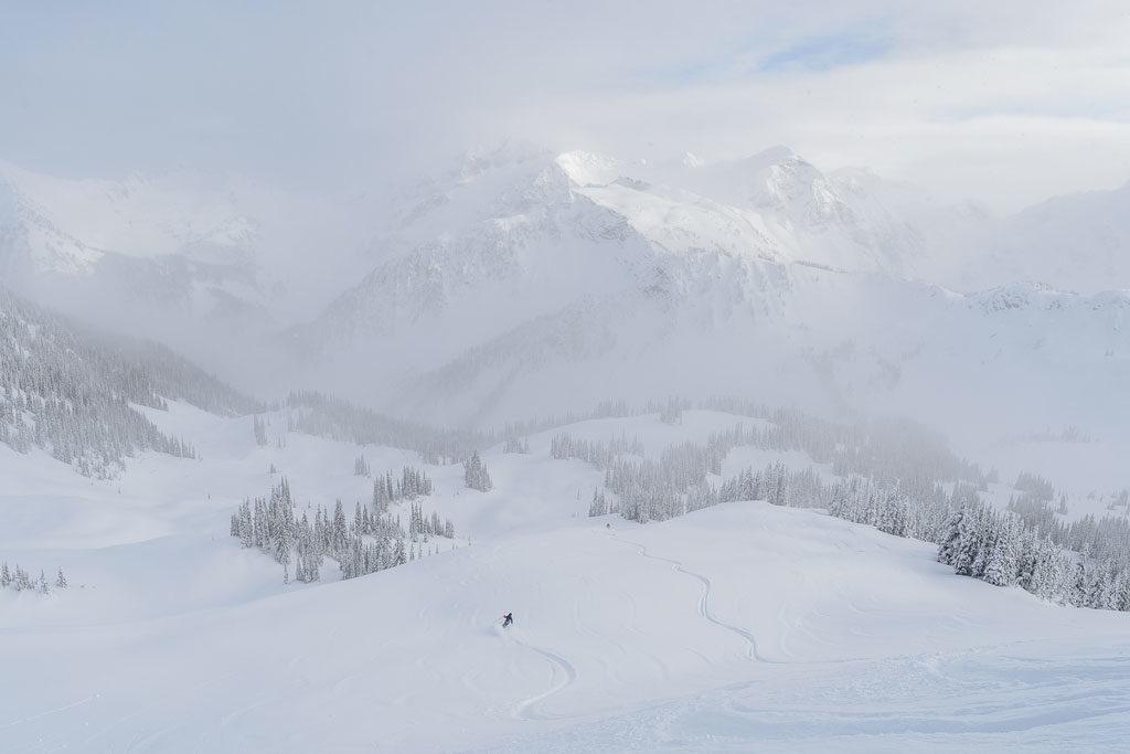 A skier carves a fresh path through a snow-covered landscape.