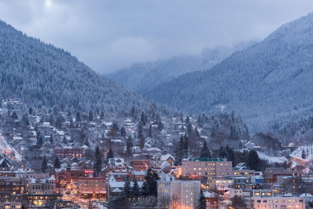A quaint mountain town under a fresh dusting of snow at dusk.