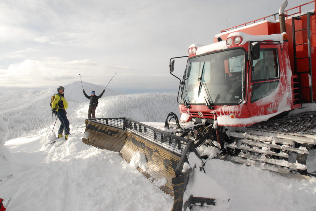 Skiers stand next to a cat vehicle on top of a mountain.