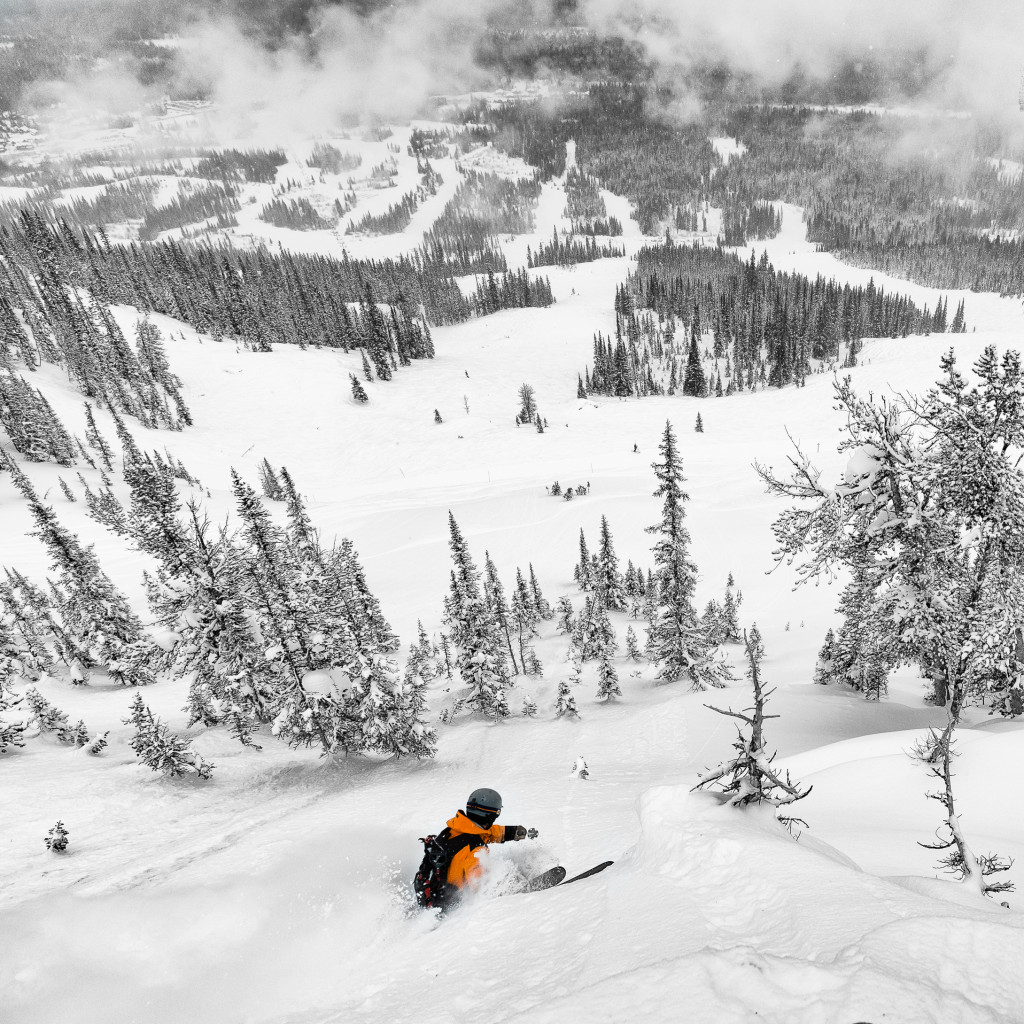 A skier travels straight down a steep slope on an overcast day.