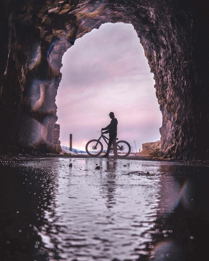 A man walks his bicycle past tunnel at sunset.