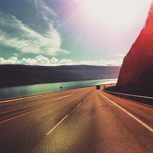 A winding coastal highway under a bright sun.