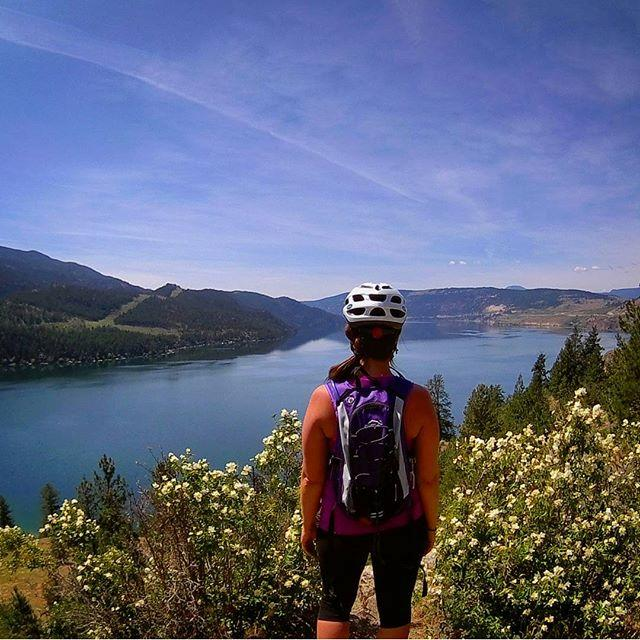 A woman wearing a bike helmet pauses to take in sweeping views of the water.