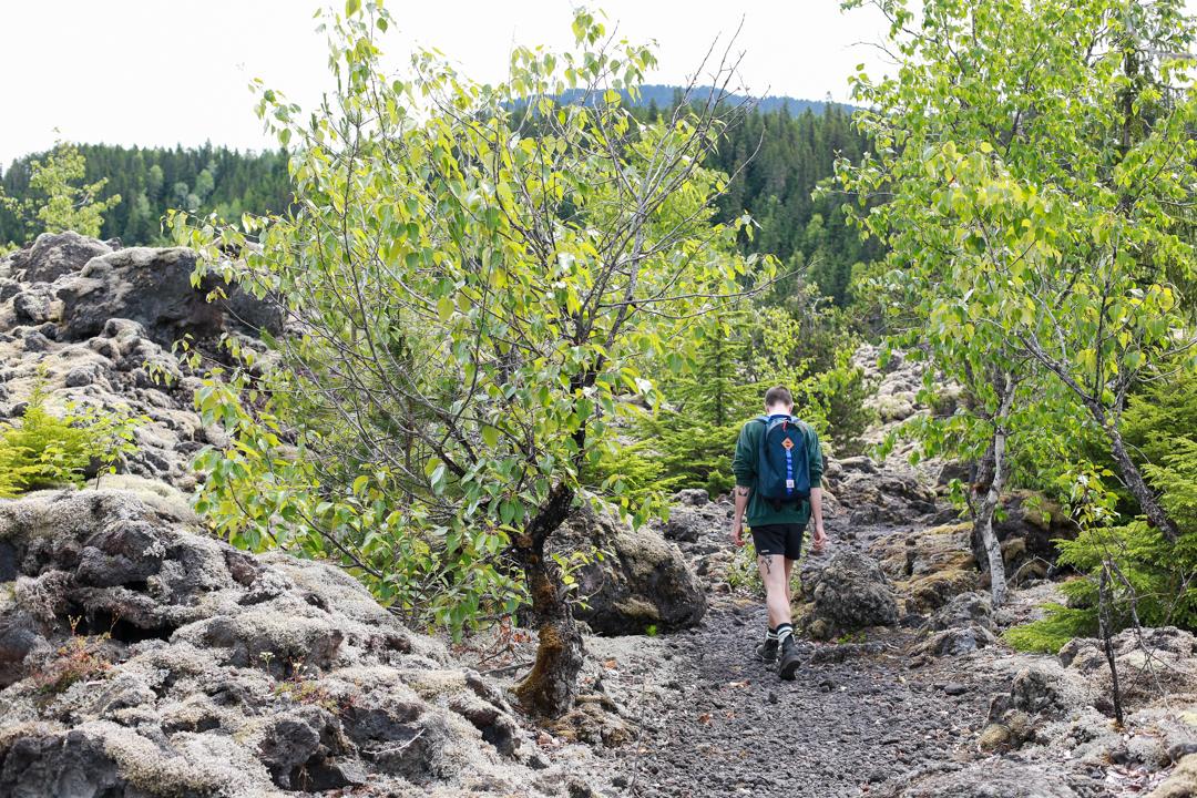 A hiker walks through old lava fields.