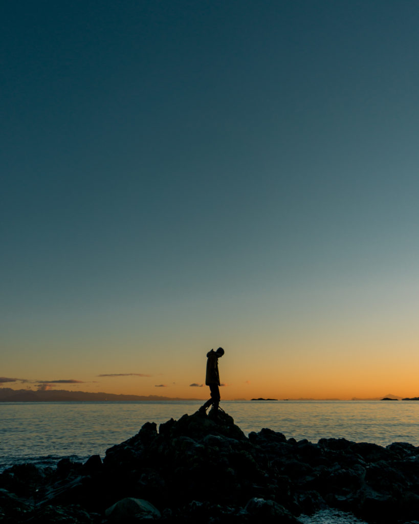 Silhouette of a man standing on a rock in front of the ocean at sunrise.