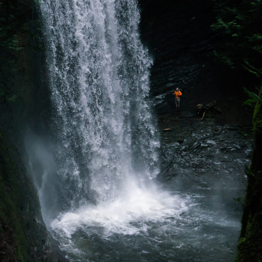 A woman in an orange jacket is dwarfed by a stunning waterfall.