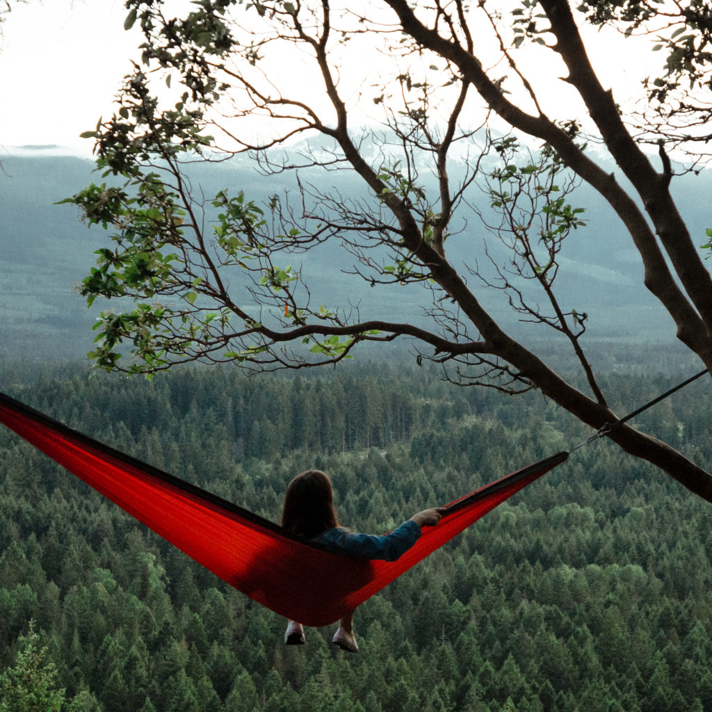 A woman relaxes in a hammock, enjoying views of the forest.