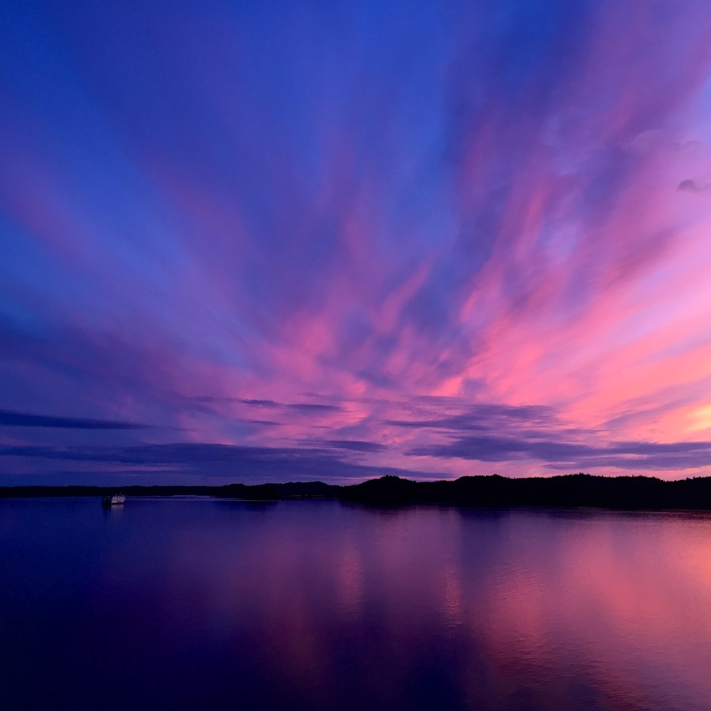A magnificent purple and pink sunset lighting up the sky in Prince Rupert and reflecting into the calm ocean.