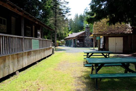 The outside of Sooke Region Museum, with a wooden fence on the left, green painted wooden picnic tables to the right and a old wooden shed in the background.
