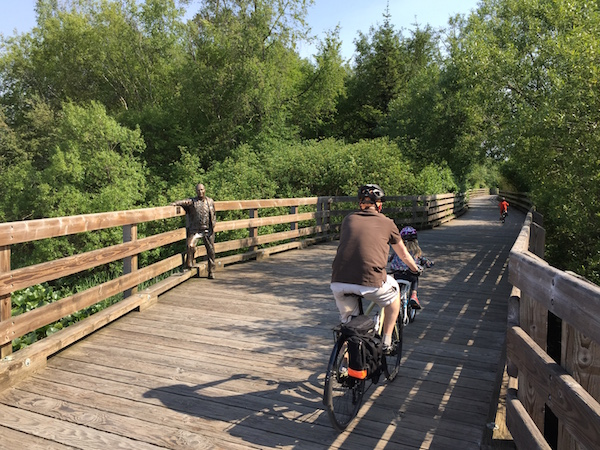 Three bikers (one man and two children) biking across the wooden trestle bridge on the Lochside Regional Trail, with a statue of the Saanich Mayor on their left.