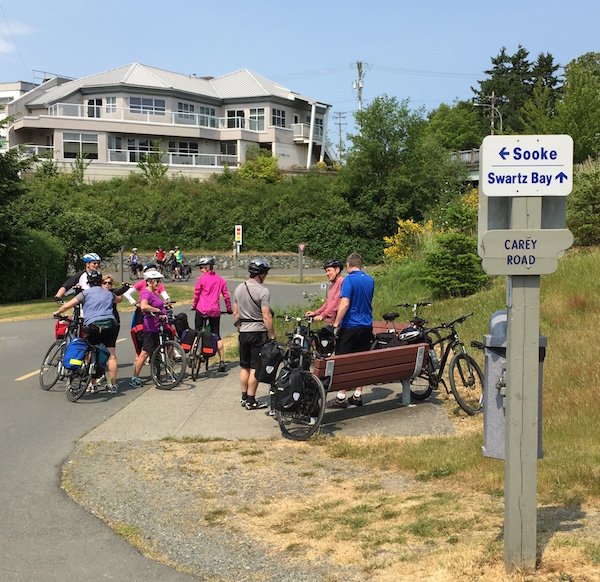 A group of eight cyclists stopped at the junction of the Galloping Goose and Lochside Regional Trails chatting with one another, with a wooden sign in the foreground with one arrow pointing to Sooke and another pointing to Swartz Bay.