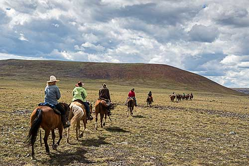 10 people riding horses all in a line through the Itcha Mountains, the majority with cowboy hats on.