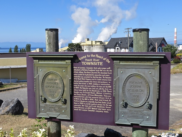 A sign commemorating Powell River's historic Townsite with the paper mill beyond.