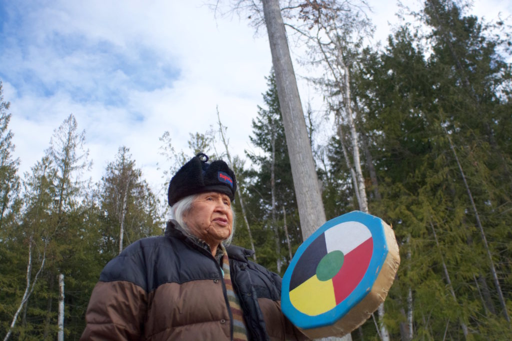 Elder Ernie Phillip drums in front of the cottonwood tree, near the town of Scotch Creek in BC's Shuswap.