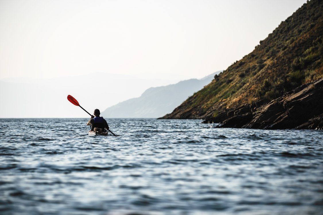 A person kayaks in calm waters off a hilly shore.