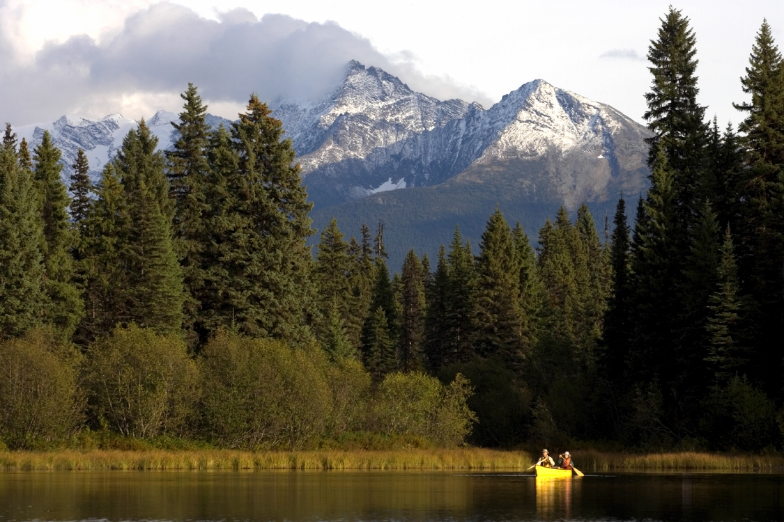 Two people in a canoe off a forested shore with mountain peaks in the distance.