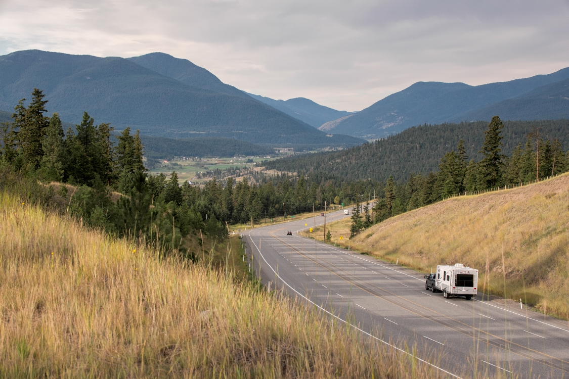 A truck towing a camper down a highway with rolling mountains beyond.